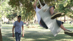 Father and a son swinging in a park Stock Video Footage