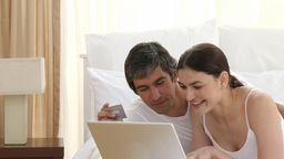 Couple in bed shopping online Stock Video Footage