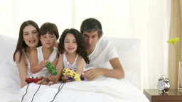 Family playing video games in bedroom Footage
