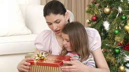 Close up of mother and daughter opening Christmas  Footage