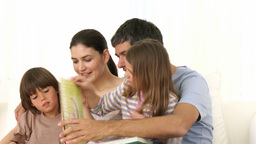 Family sitting on sofa reading a book together Footage
