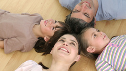 Family lying on floor with heads together at home Footage