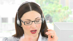 Woman speaking to a customer on a headset in the o Footage
