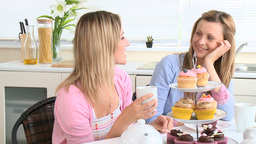 Laughing women sitting in the kitchen drinking Stock Video Footage