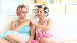 Amused woman with hair roller watching tv with her Stock Video Footage