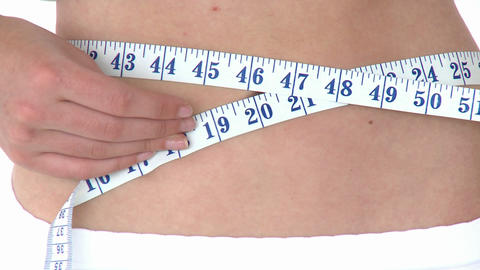 Positive woman measuring her waist with a tape mea Stock Video Footage