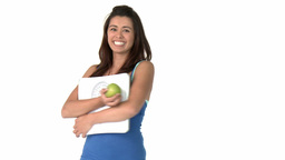Fit young asian woman holding scales and apple Stock Video Footage