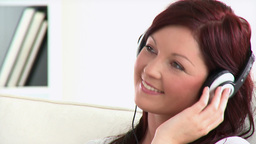 Relaxed woman with headphones on a sofa Footage