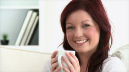 Beautiful woman holding a cup sitting on a sofa Stock Video Footage