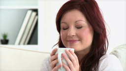 Beautiful woman holding a cup sitting on a sofa Footage
