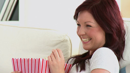 Laughing caucasian woman eating popcorn on a sofa Stock Video Footage