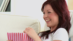 Laughing caucasian woman eating popcorn on a sofa Footage