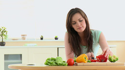 Concentrated woman cutting vegetables in the kitch Footage