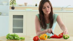 Concentrated woman cutting vegetables in her kitch Footage