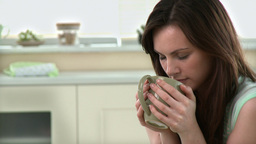 Pensive woman drinking coffee in the kitchen Stock Video Footage