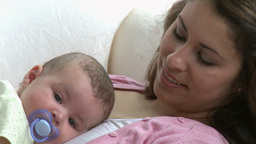 Pretty young mother lying on a sofa with her baby Stock Video Footage