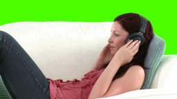 Woman listening to music lying on a sofa Footage