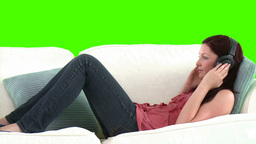 young woman lying in a sofa against listening musi Footage