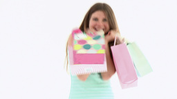 cheerful woman with shopping bags against a white  Footage
