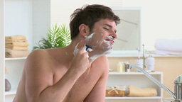 Caucasian man shaving in the bathroom Footage