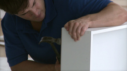 Serious man building a piece furniture Footage