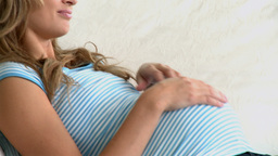 Smiling pregnant woman lying on a sofa and touchin Footage