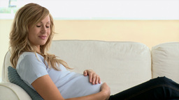 Happy young pregnant woman touching her belly lying on a sofa Footage