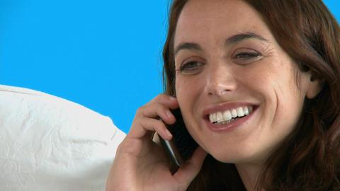 Happy hispanic woman talking on phone on the sofa Footage