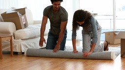 Couple rolling a carpet Stock Video Footage