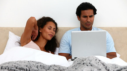 Couple enjoying using laptop in bed Live Action