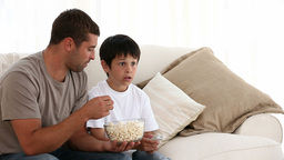 Father eating popcorn with his son Footage
