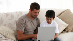 Father and son looking at the laptop Footage