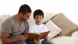 Father and son looking at a book on the sofa Stock Video Footage