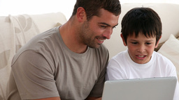 Father and son playing with a computer Footage