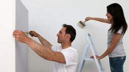 Couple painting wall in white Footage