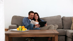 Happy couple looking at a tablet Live Action