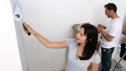 Couple painting a big wall in white Stock Video Footage