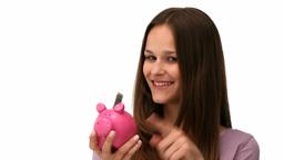Woman putting money into a piggybank Footage