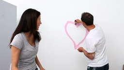 Man drawing a heart on the wall Footage
