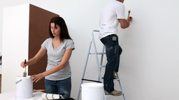 Couple painting a wall in white Footage