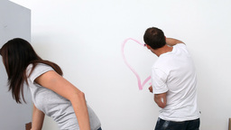 Husband drawing a heart on the wall Stock Video Footage