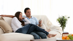 Couple watching tv on the couch Stock Video Footage
