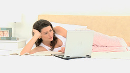 Pretty woman with a laptop on her bed Stock Video Footage