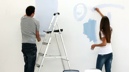 Happy couple painting wall in blue Footage