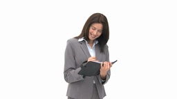 Pretty businesswoman writing on her agenda Stock Video Footage