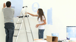 Young couple having fun while painting walls Footage