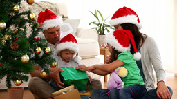 Cute family opening Christmas gift sitting on the  Footage