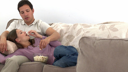Nice couple watching television with popcorn Footage