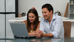 Cute happy couple looking at the laptop while sitt Stock Video Footage