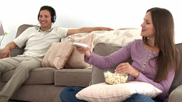 Woman watching tv with popcorn while her husband l Footage